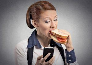 девушка ест и смотрит в телефон